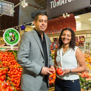 2 Gerardo Reyes Chavez of CIW and Felis Andrade of Giant Food place a Fair Food Program sign next to tomatoes in Giant's O Street store in Washington DC. Photo credit Helena Coutinho